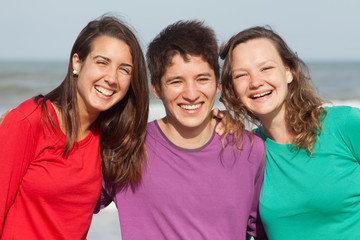 group of happy youth at the beach