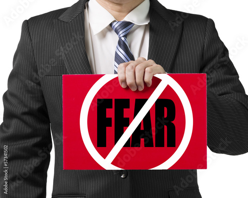 "Businessman use one hand to hold a red board with ""No Fear"" conc"