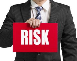"Businessman use one hand to hold a red board with word ""risk"" cl"