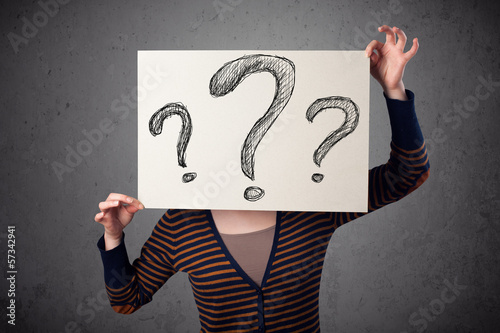 Woman holding paper with drawed question marks in front of her h