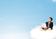 Businessman sitting on cloud with copy space