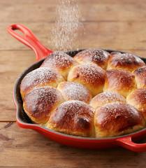 Pouring glasse sugar in brioche ball pie in a pan