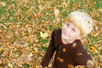 Happy Child in Falling Leaves