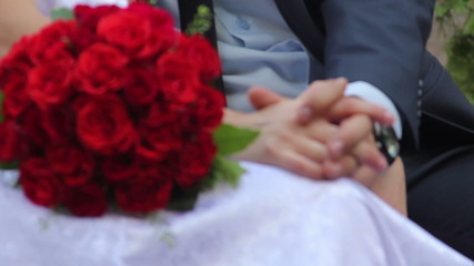 Newlyweds bride and groom on bench with bouquet of roses
