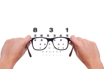 zwei Hände halten eine Brille beim Sehtest