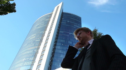 Stock broker businessman talks business phone, office building