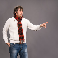 Man in sweater pointing his finger on a gray background