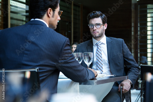 Two smiling business men have dinner at restaurant