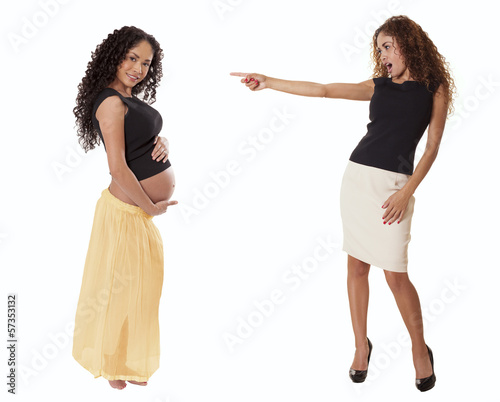 A fit business woman in a skirt points with shock at a pregnant