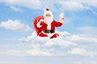 Santa Claus seated on clouds holding bag and waving with his h