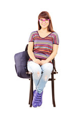 Smiling female student with school bag sitting on a chair