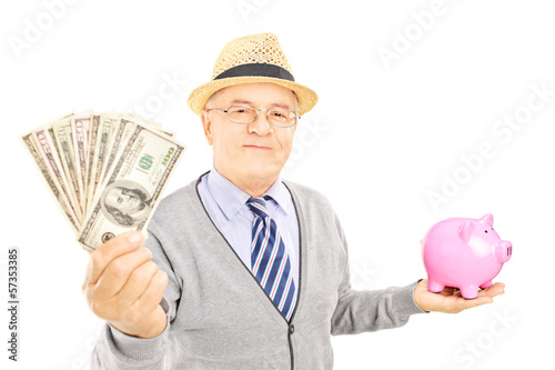 Mature gentleman holding a piggy bank and US dollars