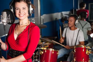 Female singer recording a track in studio