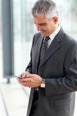 senior businessman texting