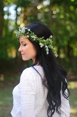 Portrait of a young woman with long black hair and flower crown