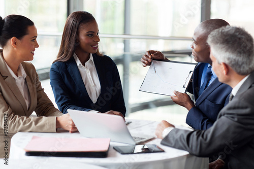 african businessman explaining sales graph to colleagues