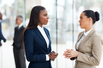 female colleagues having conversation in office