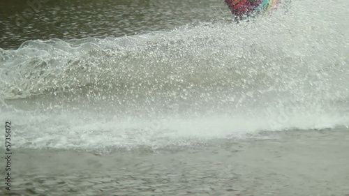 Wake-boarder in colorful sport suit rides water track splashes
