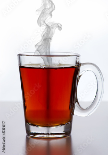 Glass cup of tea against white