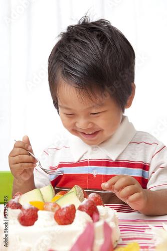 嬉しそうにベースデーケーキを見る子供