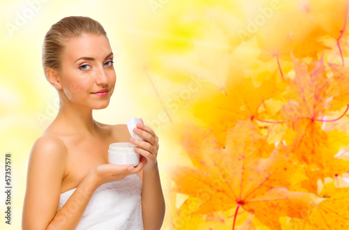 Young girl with body cream on autumnal background
