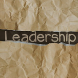 hand drawn  leadership words on crumpled paper with tear envelop