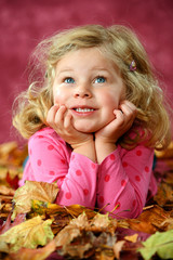 girl is lying in autumn foliage