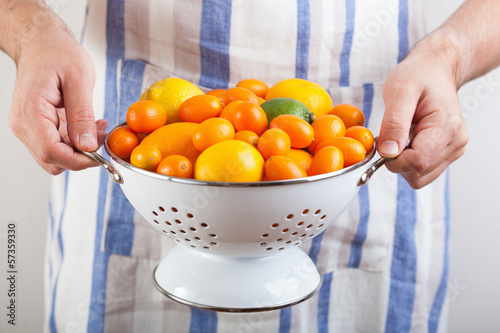 man hands holding colander with citrus fruits