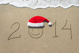 happy new year 2014 with smiley face in christmas hat on sandy b