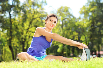 Smiling female athlete stretching in a park