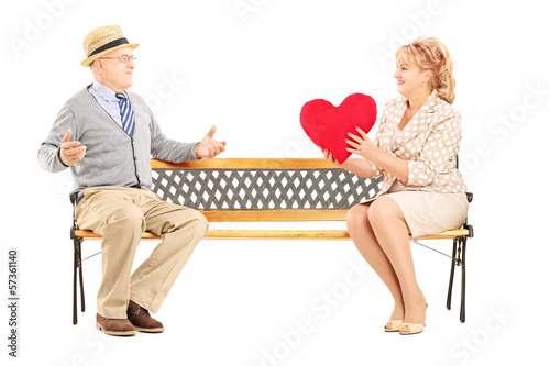 Mature female giving a red heart to a surprised man, on a bench