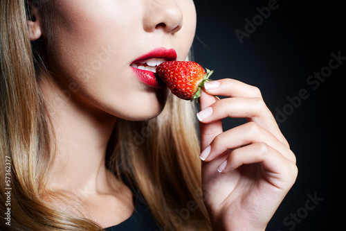 Beautiful young woman tasting strawberry