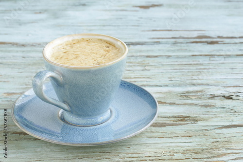 Blue cup of cappuccino on vintage wooden background