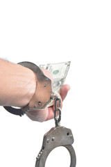 hand with handcuffs holding money