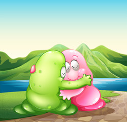 A green and a pink monster hugging each other at the riverbank