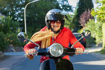 Senior lady riding her scooter.