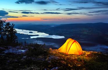 .A tent lit up at dusk