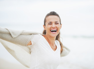 Smiling young woman in sweater having fun time on lonely beach