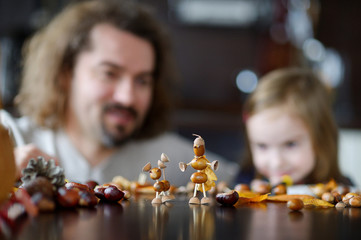Father and his kid making chestnuts creatures