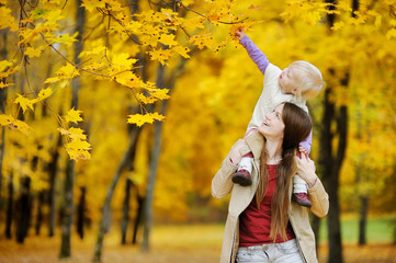 Young mother and toddler girl have fun at autumn