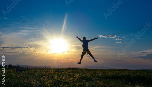 Silhouette man jumping with open arms on sundown - sunrise