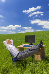 Businessman Relaxing Feet Up Desk in Green Field