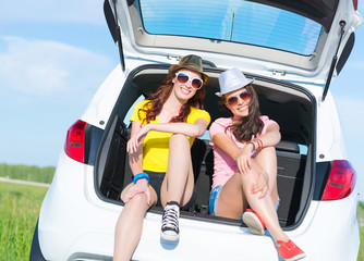 young attractive woman sitting in the open trunk