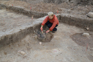 The female archeologist works at excavation with the ancient cen