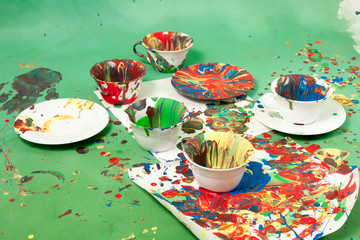 Cups with saucers all smudged with paint on a green background