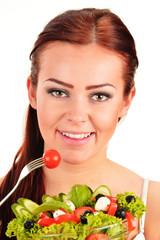 Young woman eating vegetable salad