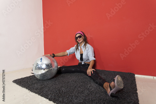 Young Woman with disco ball Over red background