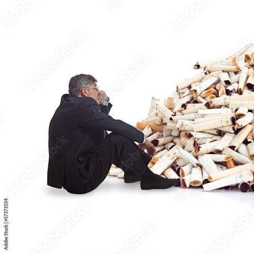 adult man thinking in front of a bunch of cigarette butts