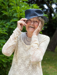 Laughing elderly lady wearing a hat.