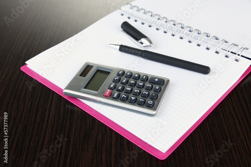 Notebook with pen and calculator on wooden background